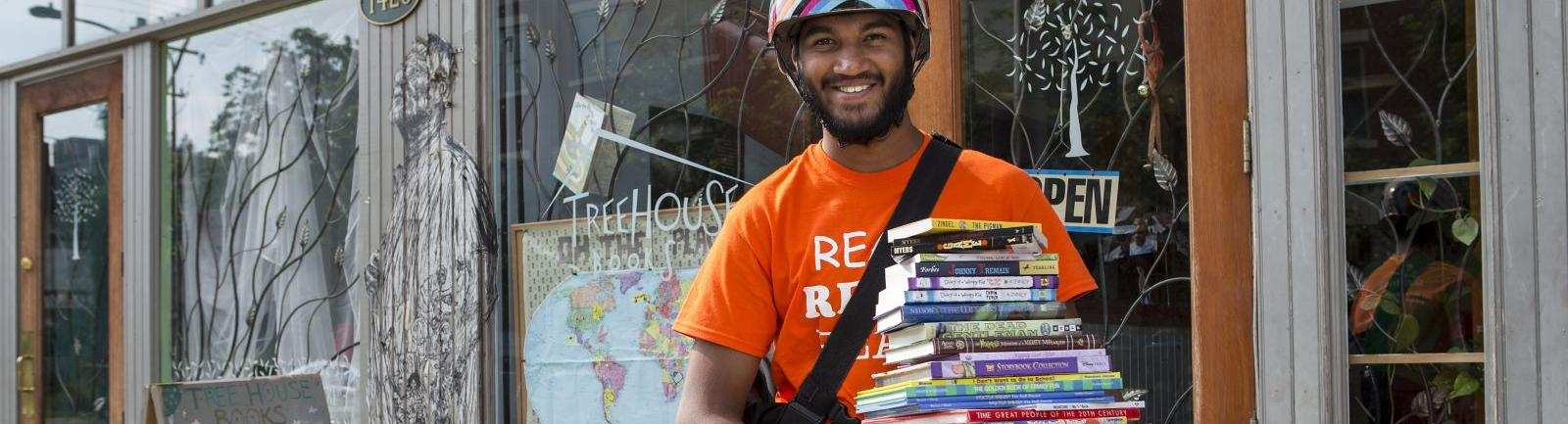 man carrying a tall stack of books on his bike
