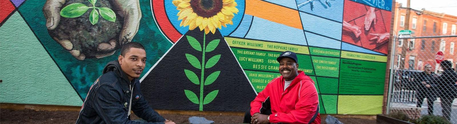 two men sitting in front of a mural on Bouvier Street