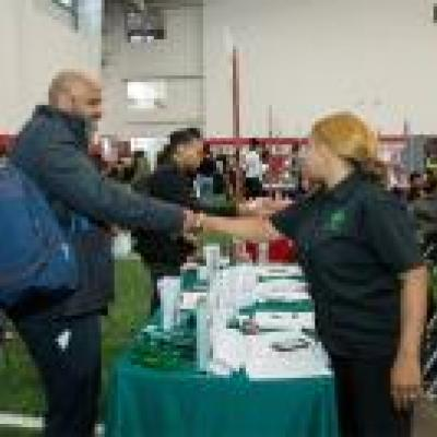 Two job fair participants shake hands.
