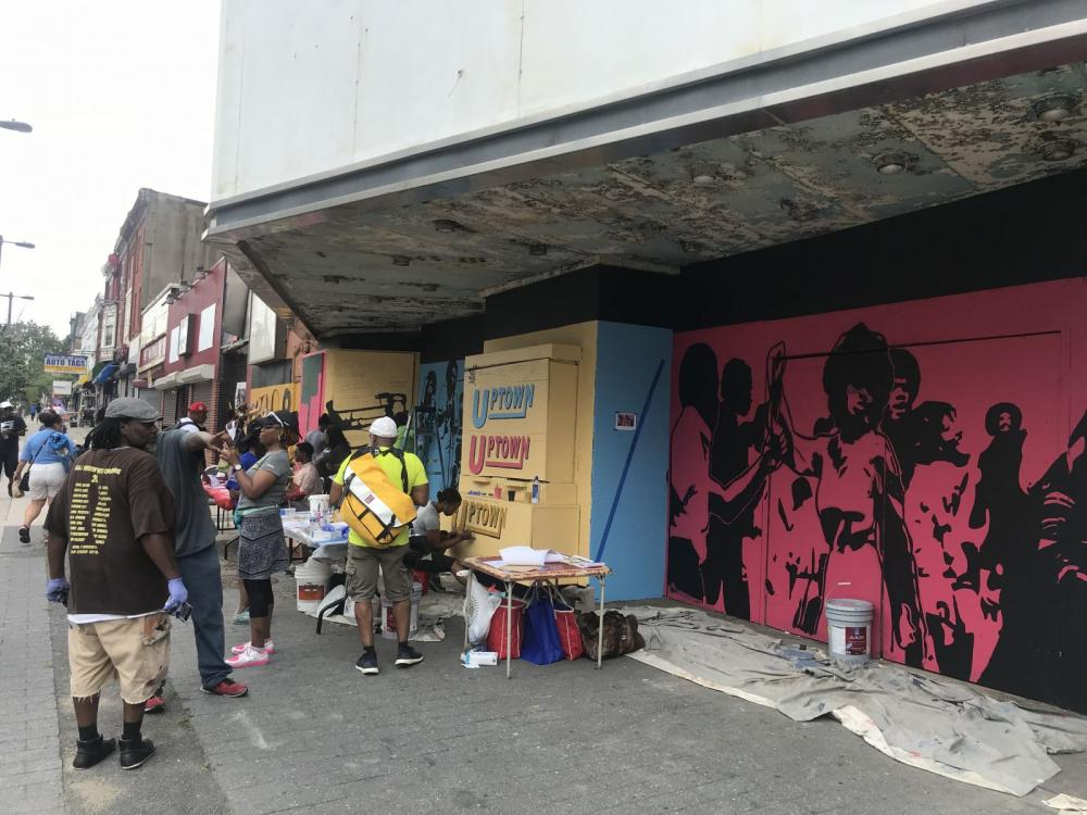 community members painting a mural at the Uptown Theater